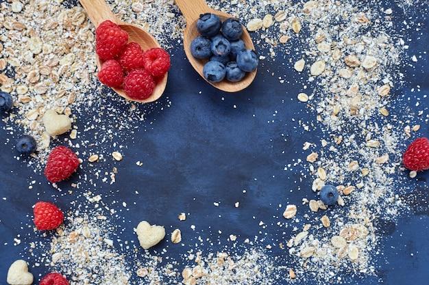 Framboesas e mirtilos em fundo azul. cereais.