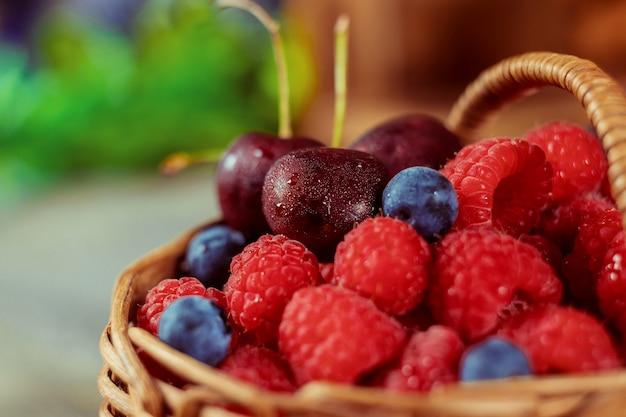 Framboesas e mirtilos em uma cesta com alça e duas cerejas