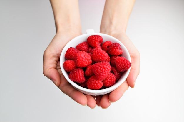 Framboesas em uma tigela na mão sobre um fundo branco isolamento feminino mão segurando uma framboesa framboesa vermelha na mão alimentação saudável, dieta alimentar vegetariana e conceito de pessoas