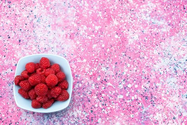 Framboesas frescas de vista de cima dentro da placa azul na vitamina de cor de frutas vermelhas de fundo colorido