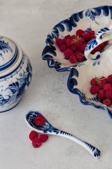 Framboesas frescas em gzhel tradicional.