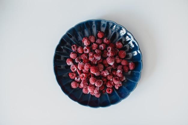 Framboesas frescas em uma placa bonita azul escuro em um fundo branco. o conceito de vegetarianismo e alimentação saudável