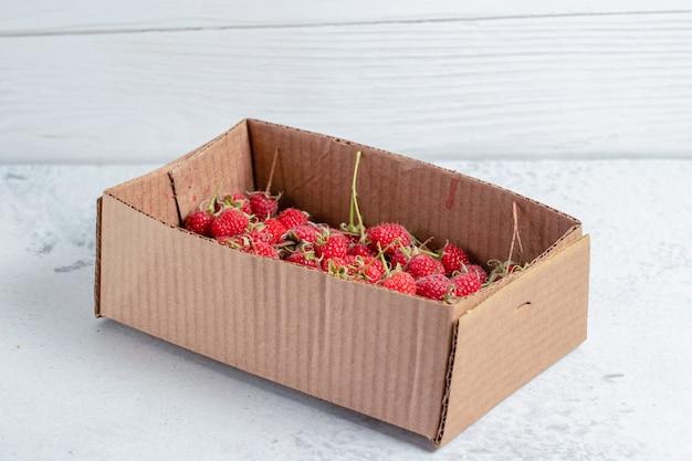 Framboesas frescas em uma superfície de cobertura cinza.