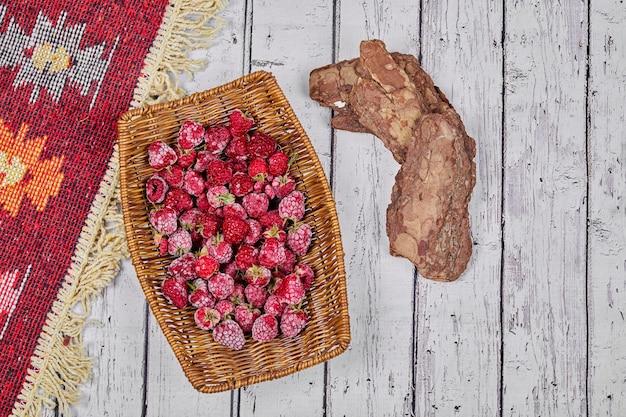 Framboesas frescas saudáveis em uma cesta de madeira com tapete esculpido.
