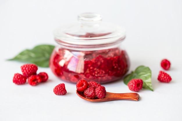 Framboesas frescas saudáveis, geléia caseira em uma jarra
