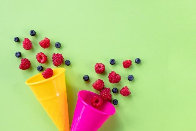Framboesas maduras e doces e mirtilos em cones de waffle de sorvete, copie o espaço