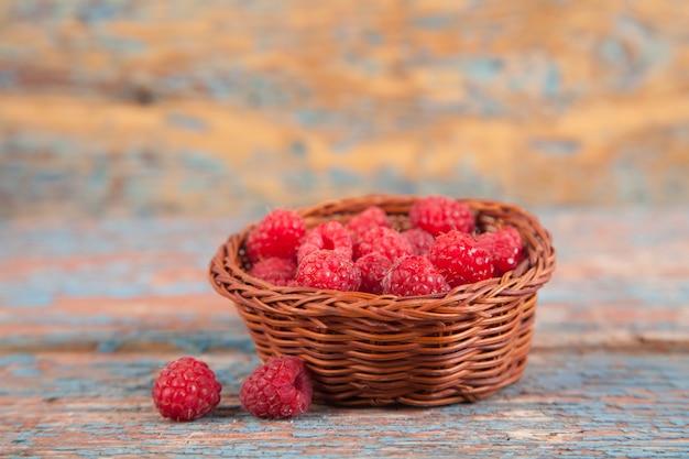Framboesas maduras suculentas em uma cesta de vime pequena em um fundo de madeira velho