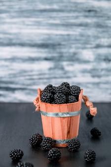 Framboesas pretas uma cesta de madeira e na mesa de madeira preta. copyspace.