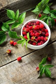 Framboesas vermelhas em uma mesa de madeira rústica desintoxicação natural fruta sobremesa dieta saudável conceito