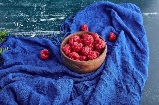 Framboesas vermelhas em uma tigela de madeira.
