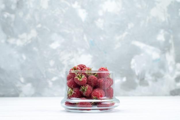 Framboesas vermelhas frescas dentro de uma tigela transparente em branco