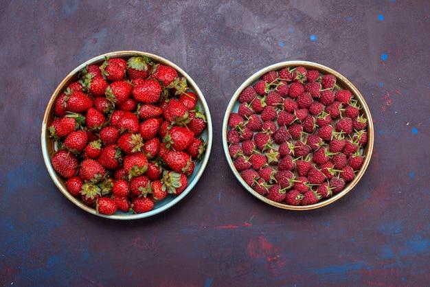 Framboesas vermelhas frescas e frutas vermelhas maduras e ácidas com morangos em uma superfície azul escura