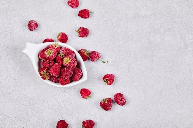 Framboesas vermelhas frescas em uma tigela branca na superfície branca. vista do topo.