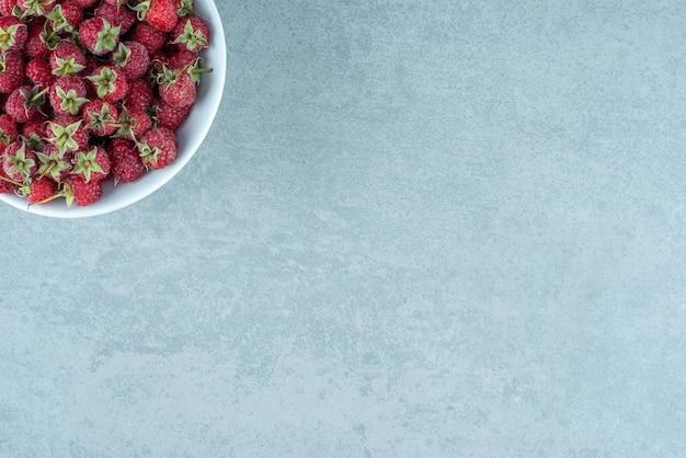Framboesas vermelhas frescas em uma tigela branca.