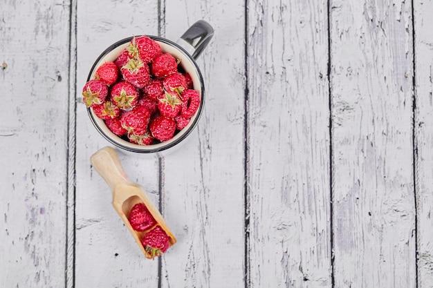 Framboesas vermelhas frescas na caneca na mesa de madeira.