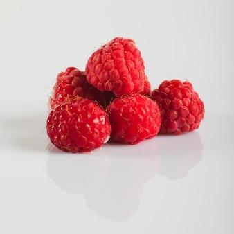 Framboesas vermelhas frescas no fundo branco