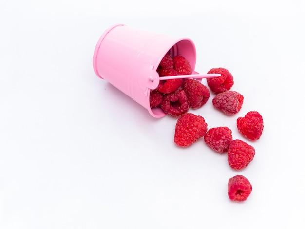 Framboesas vermelhas maduras estão caindo de um balde rosa.