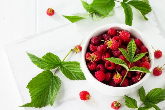 Framboesas vermelhas na mesa de madeira da cozinha sobremesa de frutas e dieta saudável