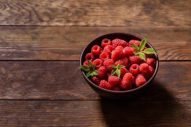 Framboesas vermelhas suculentas frescas deliciosas em uma mesa escura