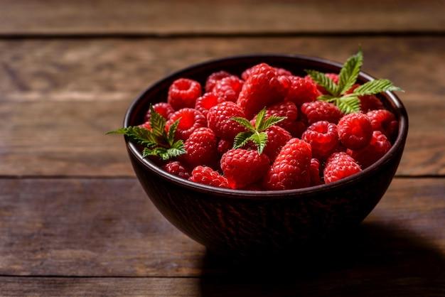 Framboesas vermelhas suculentas frescas deliciosas sobre uma mesa escura. bagas e frutas sazonais