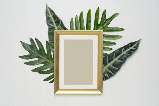 Frame da foto do ouro e folhas verdes em um fundo branco.