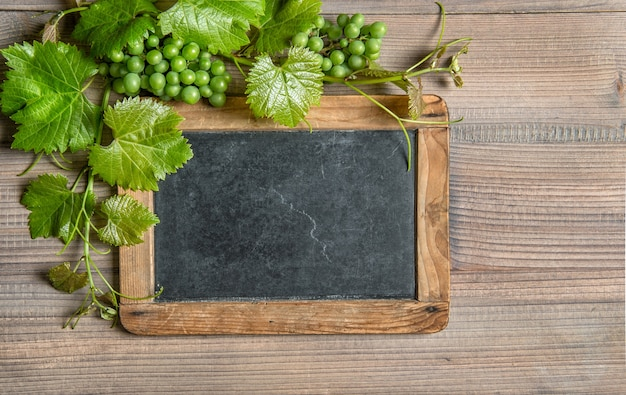 Frame de madeira com uvas e decoração de folhas de videira verde na mesa de madeira
