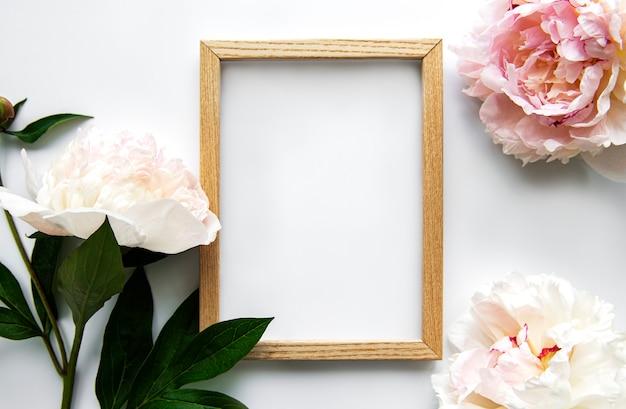 Frame de madeira rodeado por belas peônias rosa em um fundo branco, vista superior, cópia espaço, flat leigos. cartão de maquete, convites para férias ou casamento. conceito de flor de verão brilhante.