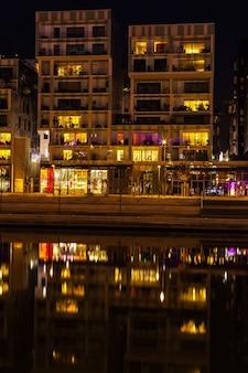 França, lyon - 19 de fevereiro: o distrito de confluence em lyon, frança, em 19 de fevereiro de 2013. novo distrito com uma arquitetura moderna no lugar do antigo porto. foto noturna