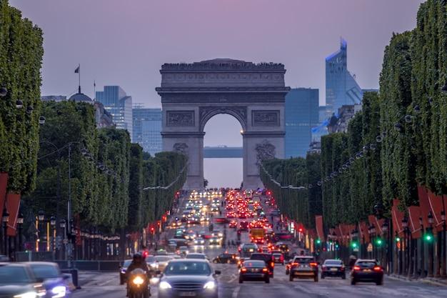 França. paris. tráfego intenso na champs elysees. arco do triunfo. crepúsculo