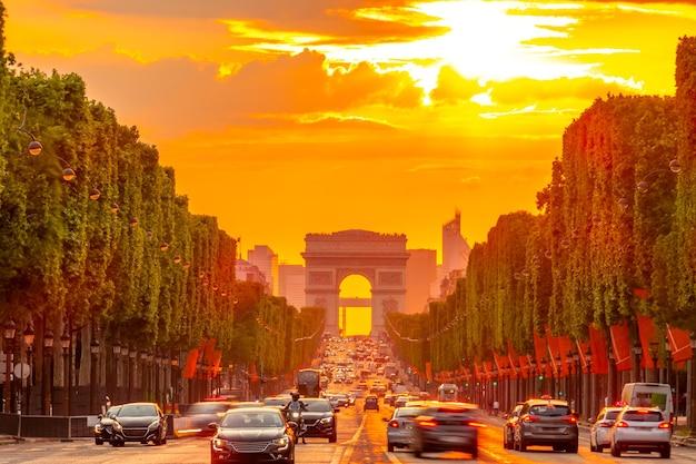 França. pôr do sol dourado de verão na champs elysees em paris. arco do triunfo e tráfego de automóveis