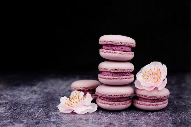 Francês macaron cookies sobremesa rosa lilás sobre um fundo escuro w