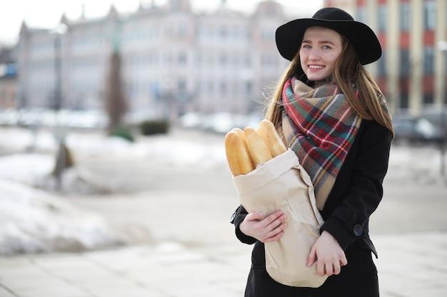 Francesa com baguetes na sacola saindo da loja