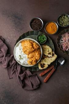 Frango à manteiga indiana com arroz basmati, especiarias, pão naan. salada de cebola