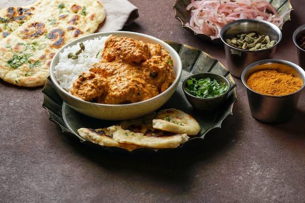 Frango à manteiga indiana com arroz basmati, especiarias, pão naan