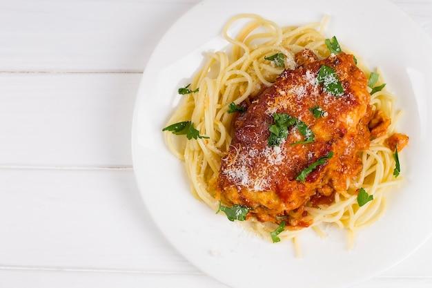 Frango à parmegiana em um prato branco com espaguete.