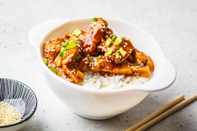 Frango asiático do teriyaki com arroz, sésamo e cebolas verdes na bacia branca.