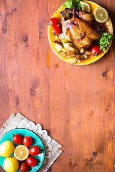 Frango assado caseiro com limão e batatas em um fundo de madeira