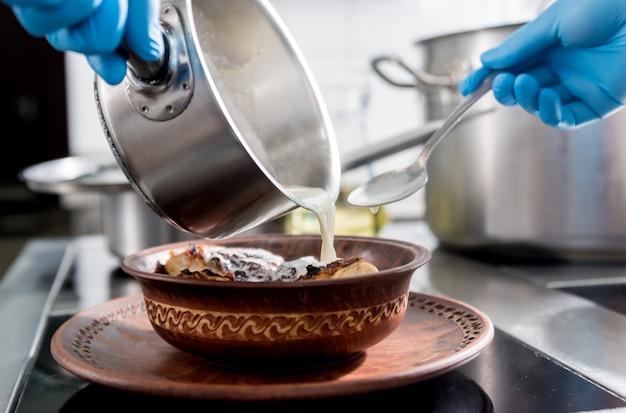 Frango assado com batata e legumes no fogão da cozinha.