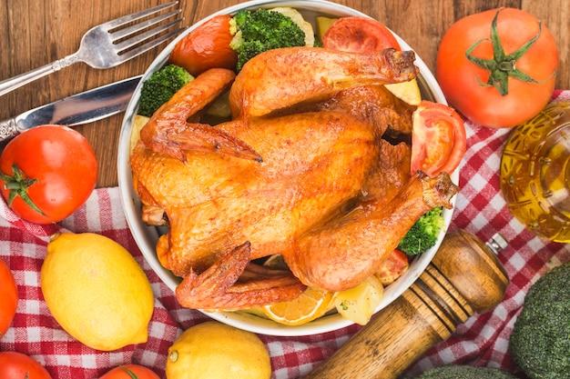 Frango assado com legumes na mesa de madeira