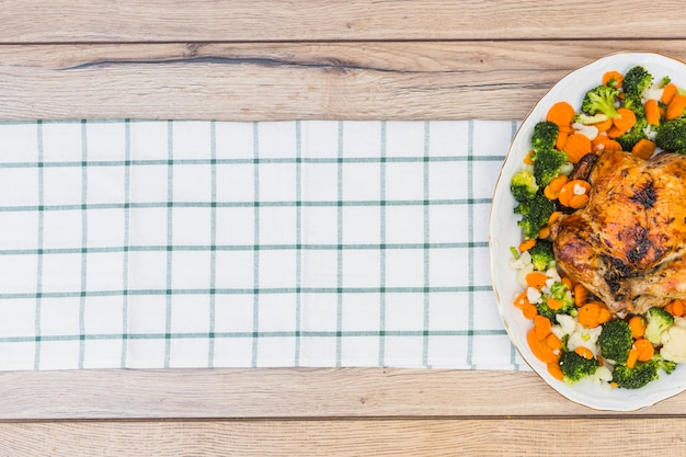 Frango assado com legumes na mesa