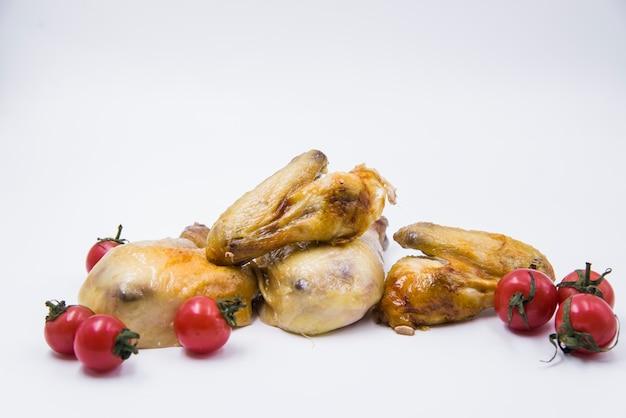 Frango assado com tomates contra isolado no fundo branco