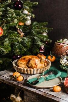 Frango assado como prato principal do feriado em uma mesa decorada com guirlanda de ano novo da família de natal ...