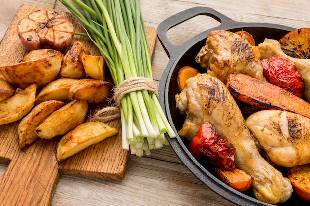 Frango assado em ângulo alto e vegetais na panela com batatas e cebolinha
