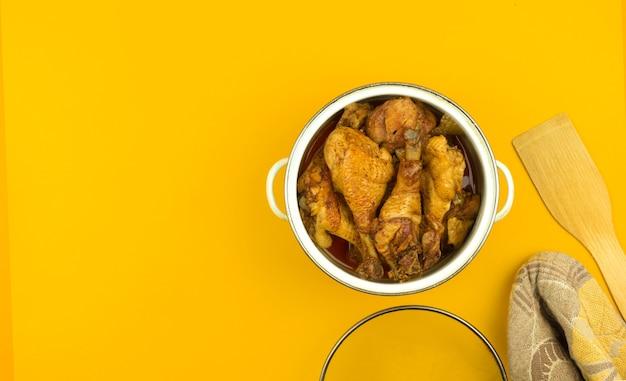 Frango assado em uma panela, coxas de frango frito para o jantar, conceito de espaço de trabalho na cozinha, plano de fundo colorido laranja com espaço de cópia, foto de vista superior