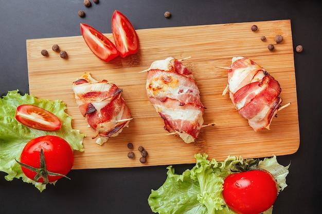Frango assado envolto em bacon. aperitivo delicioso com bacon defumado crocante. peito de frango envolto em bacon na placa de madeira. fundo preto escuro, vista superior.