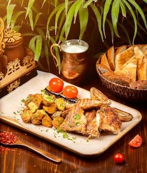 Frango assado grelhado, tabaco de frango no prato branco com batata na mesa da cozinha