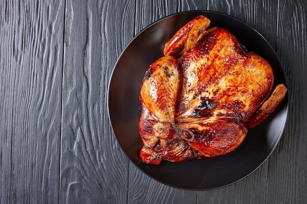 Frango assado inteiro com casca crocante marrom dourada em um prato preto sobre uma mesa de madeira para o dia de ação de graças ou jantar de natal, vista de cima, plano, close-up