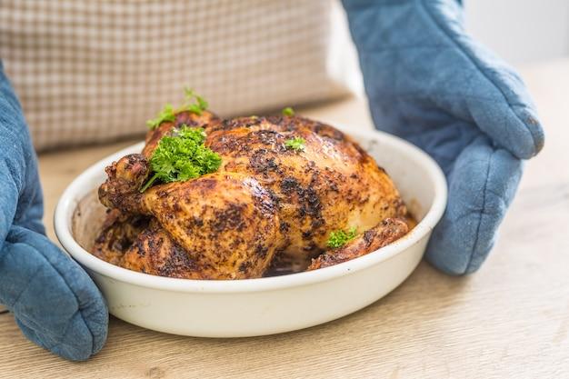 Frango assado inteiro em uma tigela segurando nas mãos cozinhe com luvas.