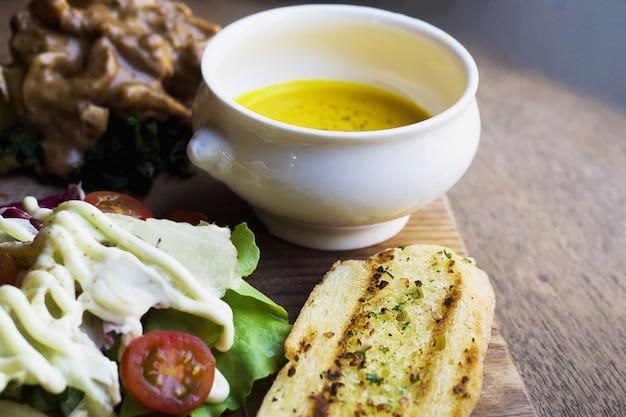 Frango assado servido com salada e pão de alho