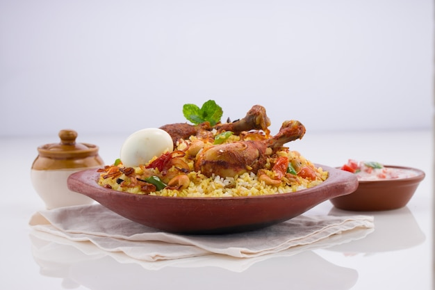 Frango biriyani usando arroz jeera arranjado em louça de barro com raitha no fundo branco
